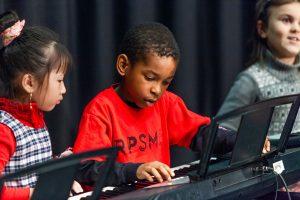3 children playing on piano